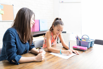 Mother Looking At Daughter Completing School Assignment At Table