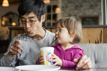Father with daughter having drinks while sitting at table in cafe