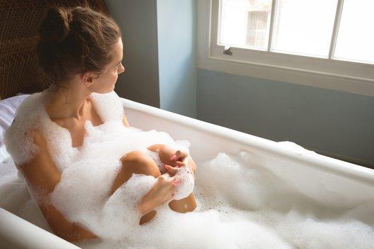 Woman taking a bath in bath tub