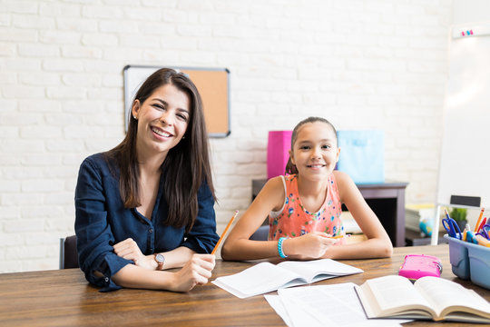 Smiling Teacher Giving Girl Private Lessons After School