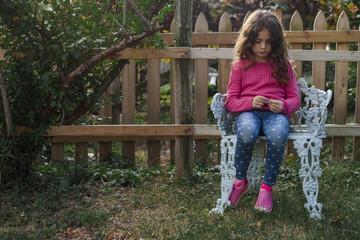 Sad girl sitting on chair in yard