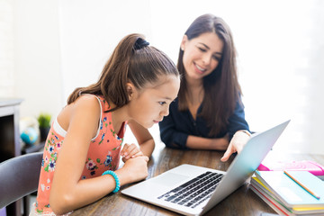 Girl And Teacher Using Laptop At Table