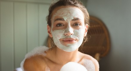 Woman with facial mask on face taking bath in bathroom