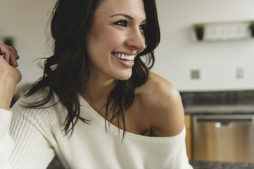Close-up of happy woman looking away while sitting against wall at home