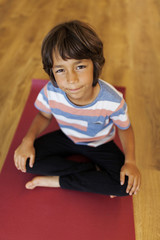 High angle portrait of boy sitting on exercise mat in yoga studio