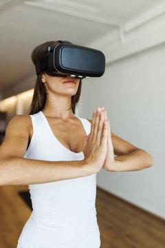 Woman wearing virtual reality simulator while meditating in yoga studio