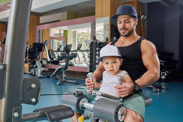 Strong dad and little son doing arms exercises sitting on metallic simulator.