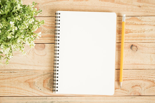 Blank notebook and yellow pencil on brown wood,Flat lay photo of notebook for your message