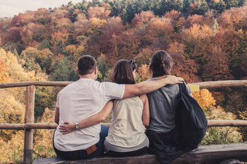 Three people hugged each other sitting on wooden benches and watch the beautiful autumn landscape, concept of polygamy