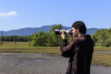 Man photographing nature in dry brazilian mangrove