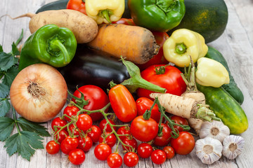 Colourful variety of fresh home grown vegetables from an organic garden on a wooden surface. Tomato, green and yellow bell peppers, carrot, parsley, onion, garlic, potato, eggplant and zucchini.