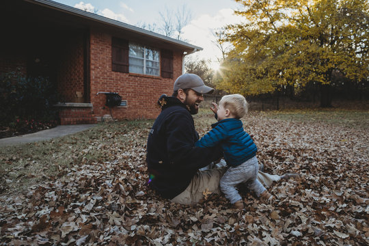 Happy father playing with son while sitting on autumn leaves at yard