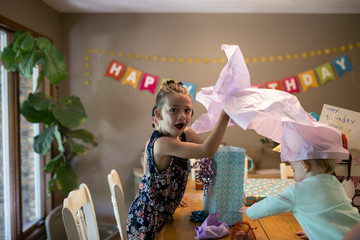 Portrait of surprised girl with sister opening birthday gifts on table at home