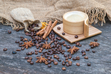 Wooden cup of coffee and coffee beans