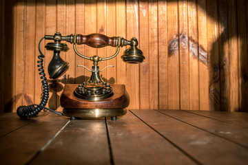 Vintage telephone on wooden table with wooden background at sun