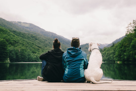 Couple sitting with a dog on dock at the lake. Back view