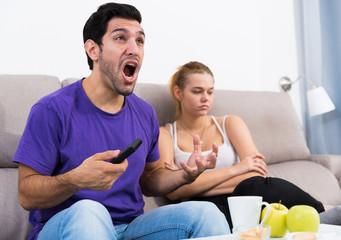 Man watching tv ignoring frustrated girl