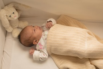 Newborn baby relaxing on baby bed