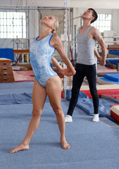 Happy woman and man acrobats training gymnastic action at gym
