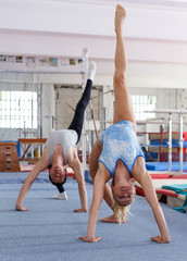 Mature woman and man gymnasts exercising gymnastic action at gym