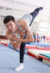 Positive man  acrobat exercising gymnastic action at sport gym