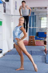 Female gymnast in bodysuit during workout in gym,  man on background