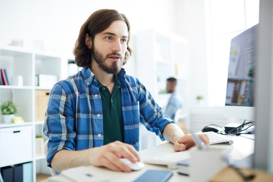 Young handsome man in casualwear working with database while sitting in front of computer monitor