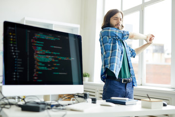 Young programmer stretching his arms while keeping hands together during break for relax in office