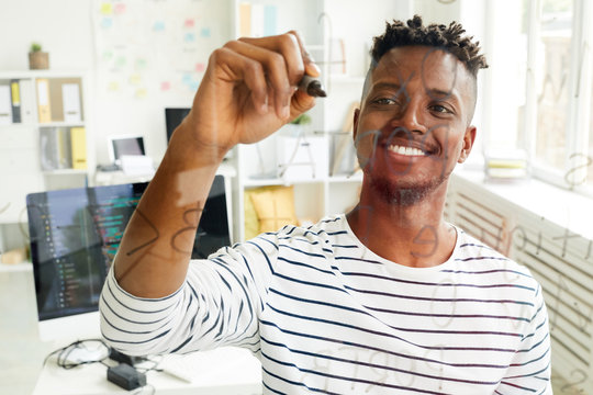 Happy young African-american it-manager with highlighter writing down software codes on board