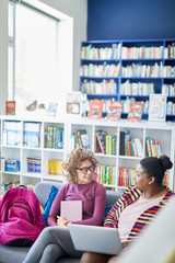 Jolly confident multi-ethnic student girls sitting on sofa with satchels and discussing plan of project in library, serious African-American overweight woman using laptop during discussion