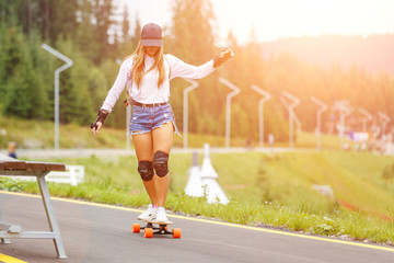 Young girl longboarding downhill on the hillside road