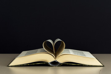 Old open book page in heart shape with library background, love in valentine day concept