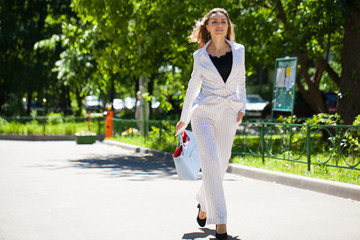 Young happy brunette woman in white business suit