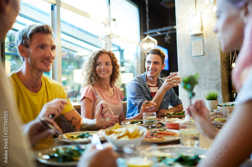 Cheerful young friendly people having talk by table served