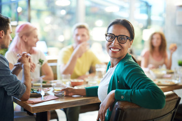 Mixed-race girl with toothy smile looking at you while sitting by served table at dinner