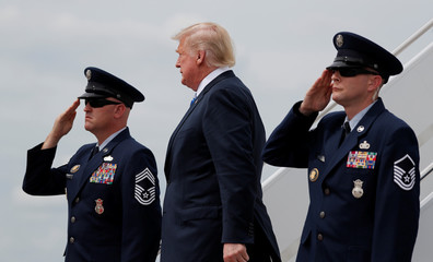 U.S. President Trump is saluted by Air Force officers as he arrives to sign the National Defense Authorization Act in Watertown, New York