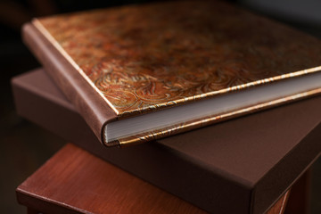 Photo book with a cover of genuine leather. Brown color with decorative stamping . Dark background. Soft focus.