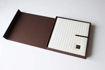Photo book with a cover of genuine leather in the box. White color with decorative stamping .Soft focus.
