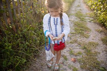 A girl looks a seed pod she has found on a beach path.
