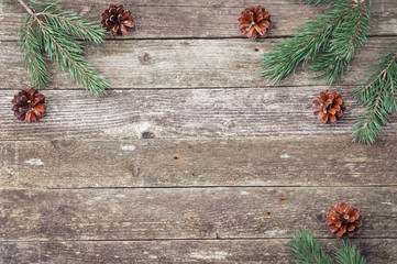 Green fir and pine branches with cones on a wooden gray texture. Christmas and New Year background. Space for text.