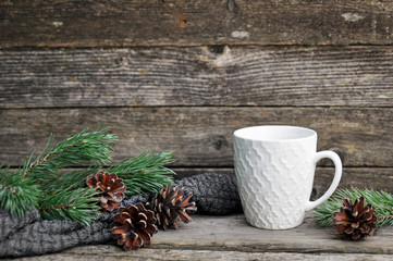 White cup with pattern, cones and green pine branches on a knitted sweater. Winter holydays. Wooden gray background. insert text