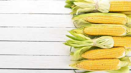 Fresh yellow corn on a white wooden table. Vegetables. Top view. Copy space.