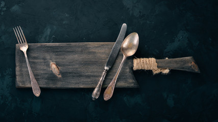 Old cutlery. On a black stone background. Top view. Free space for text.