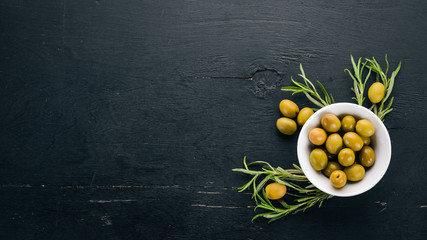 Fototapete - Olives in a plate and rosemary. On a black wooden background. Free space for text.