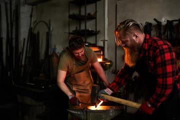 Team of brutal blacksmiths in workwear shaping metal together: bearded man hammering heated metal held by his coworker in factory shop