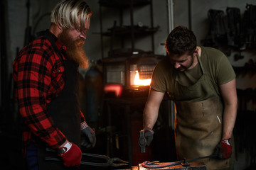 Serious brutal manual workers in aprons hammering hot iron while changing shape of heated metal together in workshop