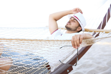 Young man resting in hammock at seaside. Summer vacation