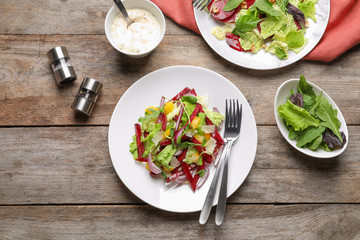 Delicious beet salad on wooden table, top view