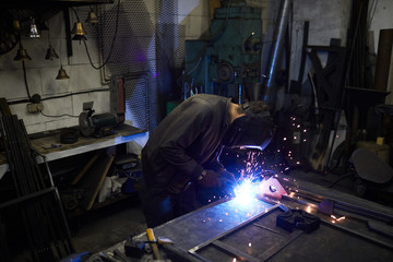 Busy worker in mask concentrated on welding process working with metal planks while joining it in frame in dark workshop