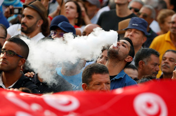 A protester smokes an electronic cigarette during a rally demanding equal inheritance rights for women, in Tunis